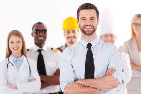 empleado de oficina: Cuando yo sea grande voy a ser un hombre de negocios. Hombre joven confidente en camisa y corbata mantener los brazos cruzados y sonriendo mientras que el grupo de personas de diferentes profesiones de pie en el fondo