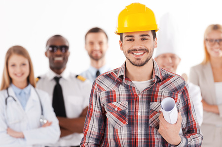 When I grow up I will be an engineer. Confident young man in hardhat holding blueprint and smiling while group of people in different professions standing in the background photo