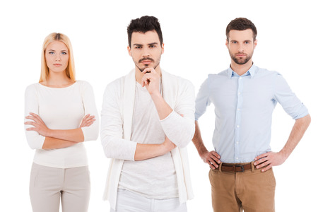 arms akimbo: Confident young professionals. Three confident young people in smart casual wear looking at camera while standing against white background Stock Photo