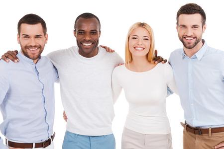 幸せなビジネスのチーム。幸せな若い人互いに接着し白背景に立ってカメラを見てスマート カジュアルな服装で
