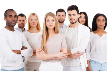 arms crossed: Confident business team. Group of confident multi-ethnic group of people in smart casual wear looking at camera while standing against white background