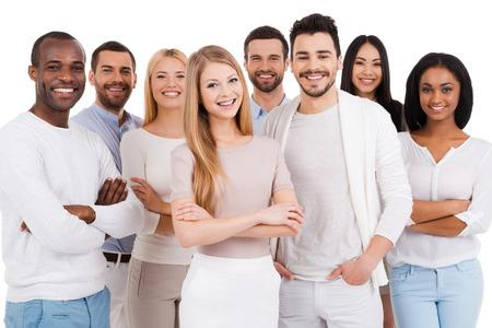 människor: Positiv professionellt team. Grupp av positiva och olika människor i smarta fritidskläder tittar på kameran och ler samtidigt som står mot vit bakgrund