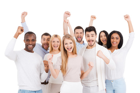 united people: Successful team. Group of happy young people in smart casual wear looking at camera and keeping arms raised while standing against white background