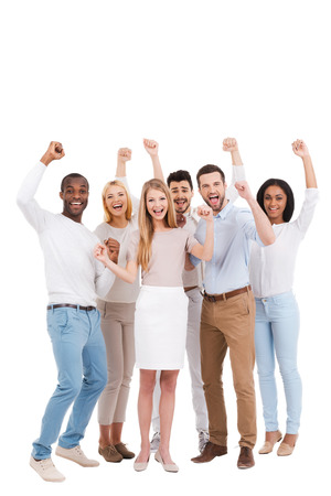 six people: Successful team. Full length of group of happy young people in smart casual wear looking at camera and keeping arms raised while standing against white background