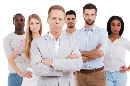 people from behind: Leading his team to success. Confident mature man in smart casual wear keeping arms crossed and looking at camera while group of young people standing behind him and against white background