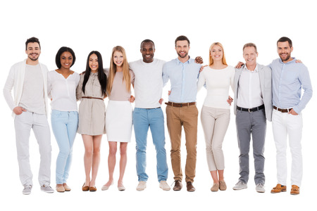 The best team ever. Full length of happy diverse group of people bonding to each other and smiling while standing against white background together