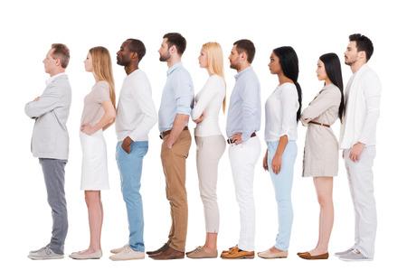 행 서. 행에서 흰색 배경에 서있는 동안 멀리보고 스마트 캐주얼에있는 사람들의 자신감을 다 인종 그룹의 전체 길이