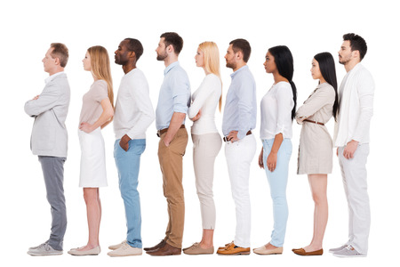 Staan in een rij. Volledige lengte van overtuigd multi-etnische groep mensen in smart casual wear wegkijken tijdens het staan in een rij en tegen een witte achtergrond Stockfoto
