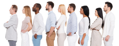 Waiting in a row. Side view of confident diverse group of people in smart casual wear looking away while standing in a row and against white background