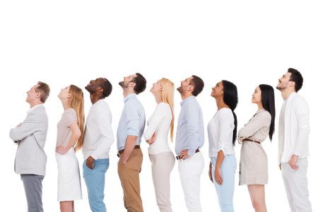 그게 뭐야? 긍정적 인 다양한 그룹의 사람들이 스마트 캐주얼 입고 나란히 서있는 동안 흰색 배경에 대해 측면보기 스톡 콘텐츠