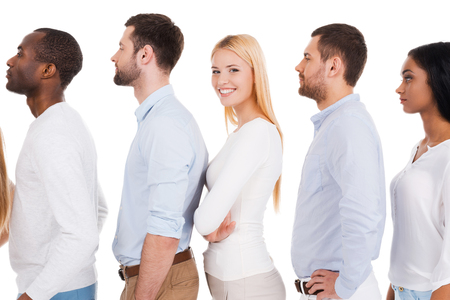 team leadership: Everyone will get a chance. Side view of beautiful young woman looking at camera and smiling while standing in a row with other people and against white background