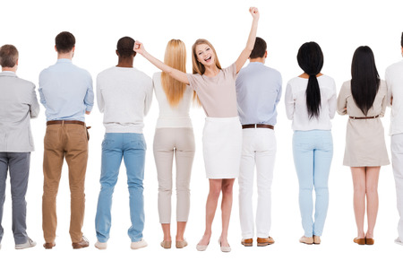 Everyday winner. Rear view of group of people standing in a row and against white background while one woman standing face to camera and expressing positivity photo