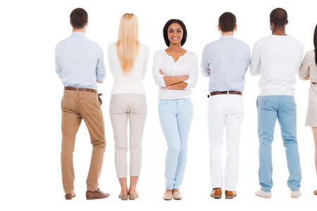 standing against: Now it is my turn. Rear view of group of people standing in a row and against white background while one beautiful African woman standing face to camera and smiling Stock Photo