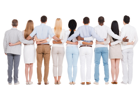 United team. Full length rear view of group of diverse people bonding to each other while standing against white background photo