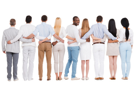 Happy to be in team. Full length rear view of group of diverse people bonding to each other and standing against white background while one African man looking over shoulder and smiling photo