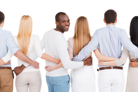 Together we are stronger! Rear view of group of diverse people bonding to each other and standing against white background while one African man looking over shoulder and smiling photo