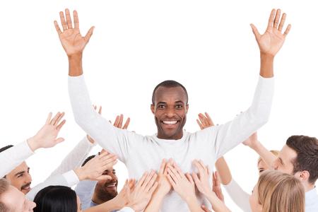 chose: Hanno scelto il loro leader. Felice giovane uomo africano in piedi contro sfondo bianco e tenendo le braccia aperte, mentre un gruppo di persone entusiaste che allunga le mani verso di lui e sorridente Archivio Fotografico