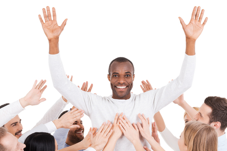 chose: They chose their leader. Happy young African man standing against white background and keeping arms outstretched while group of excited people stretching hands to him and smiling Stock Photo