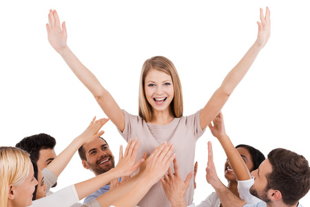 real leader: She is a real leader. Happy young woman standing against white background and keeping arms outstretched while group of excited people stretching hands to her and smiling