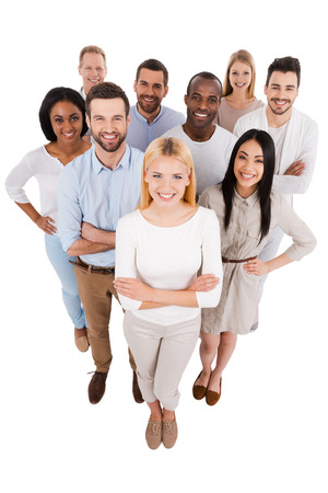 Proudly successful. Top view of positive diverse group of people in smart casual wear looking at camera and smiling while standing close to each other