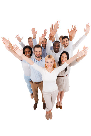 Dream team. Top view of positive diverse group of people in smart casual wear looking at camera and stretching out their hands while standing close to each other