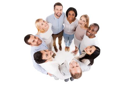 Gelukkig verenigd team. Bovenaanzicht van positieve diverse groep van gelukkige mensen in slimme vrijetijdskleding binding aan elkaar en staan in de cirkel