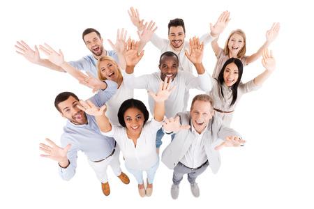 성공적인 비즈니스 팀. 스마트 캐주얼에서 사람들의 긍정적 인 다양한 그룹의 상위 뷰 카메라를보고 서로 가까이 서있는 동안 그들의 손을 뻗어