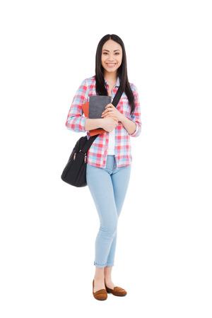 自信を持って大学生。教科書や白背景に立ちながら笑顔で若いアジアの十代の女の子の完全な長さ