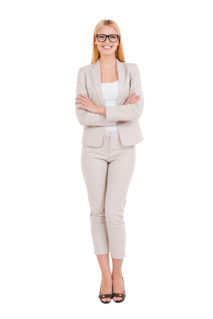 Confident businesswoman. Full length of beautiful young woman in formalwear keeping arms crossed and smiling while standing against white
