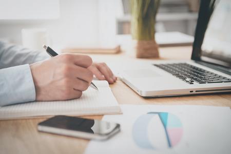 Het maken van enkele dringende notities. Close-up van man schrijven iets in zijn notitie pad tijdens de vergadering op zijn werkplek