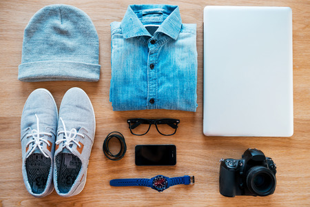 desks: Hipster collection. Top view of clothing and diverse personal accessory for hipster laying on the wooden grain Stock Photo