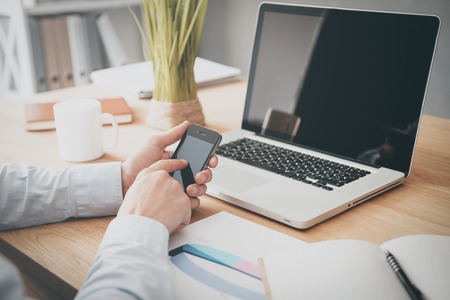 Typing business message. Close-up of man holding mobile phone while sitting at the wooden desk with laptop laying on it