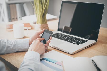 Psaní podnikání zprávu. Close-up muže, který držel mobilní telefon, zatímco sedí na dřevěný stůl s laptop, kterým se na něm