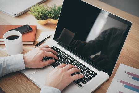 empresario: El hombre de negocios en el trabajo. Vista superior Primer plano del hombre que trabaja en la computadora port�til mientras est� sentado en el escritorio de madera
