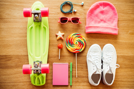 female clothing: Girls collection. Top view of clothing and diverse personal accessory for teenage girls laying on the wooden grain