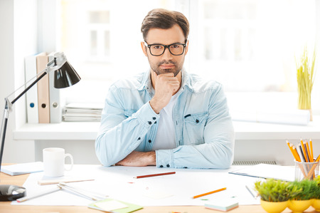 Generating new ideas. Handsome young man in shirt and eyewear holding hand on chin and looking at camera while sitting at his working place photo