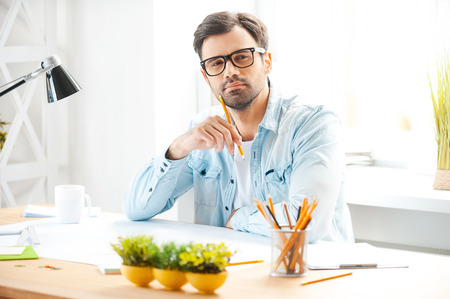Creative professional at work. Handsome young man in shirt and eyewear holding pencil near his chin and looking at camera while sitting at his working place photo