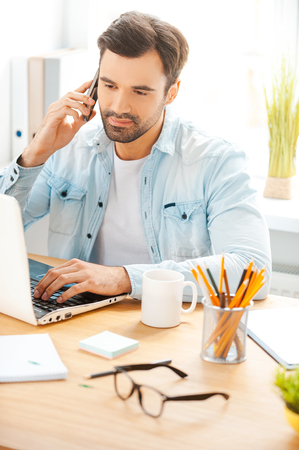 He is always hard at work. Handsome young man in shirt talking on the telephone and working on laptop while sitting at his working place Stock Photo