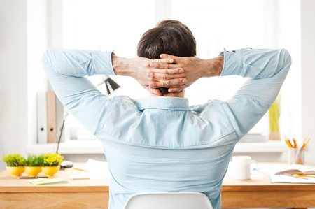 man relax: Having rest for productive work. Rear view of young man in shirt holding head in hands while sitting at his working place