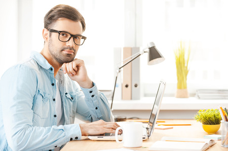 Creating new vision. Handsome young man in shirt and eyewear working on laptop and looking at camera while sitting at his working place photo