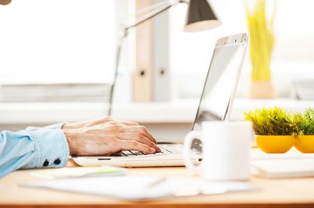 trabajando duro: Trabajando duro para cumplir con los plazos. Primer plano de hombre joven que trabaja en la computadora port�til mientras est� sentado en su lugar de trabajo