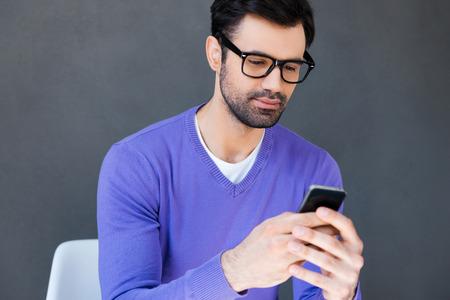 hombre pensando: Comer bien mensajería. Hombre joven hermoso que sostiene el teléfono móvil mientras se está sentado sobre fondo gris