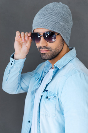 headwear: Enjoying his style. Handsome young man in eyewear and headwear posing against grey background