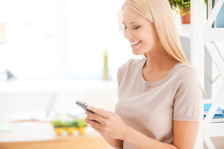 business lifestyle: Typing message to colleague. Beautiful young woman leaning at the shelf in office and smiling while holding mobile phone