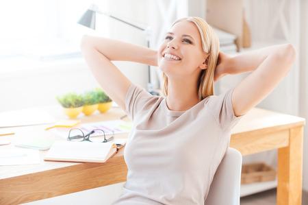 empleado de oficina: Satisfecho con el trabajo realizado. Joven y bella mujer sosteniendo las manos detr�s de la cabeza y sonriendo mientras est� sentado en su lugar de trabajo en la oficina Foto de archivo