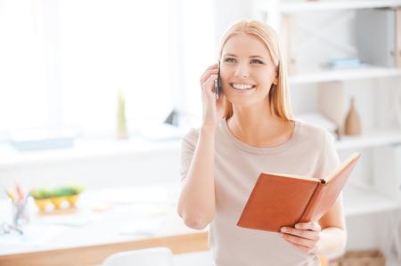 동료들과 좋은 소식을 공유. 아름다운 젊은 여자를 사무실에서 그녀의 작업 장소 근처에 서있는 동안 휴대 전화에 얘기하고 노트 패드를 들고