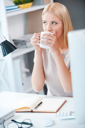 idea comfortable: Starting day with cup of fresh coffee. Beautiful young woman drinking coffee and looking away while sitting at her working place in office
