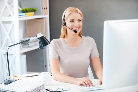 servicio al cliente: Representante de servicio al cliente en el trabajo. Joven y bella mujer en el auricular trabaja en la computadora y sonriendo mientras está sentado en su lugar de trabajo en la oficina