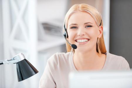 Altijd klaar om u te helpen. Gelukkige jonge vrouw in headset kijken naar de camera en glimlachen tijdens de vergadering op haar werkplek