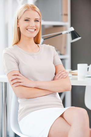 secretary desk: Making business look good. Beautiful young woman looking at camera and smiling while sitting at the chair in office